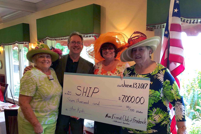 Ed Hinde and New Friends Club of Frederick holding a donation check